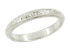 Absolutely a delight to behold, this Art Deco vintage wedding ring, circa 1920's, displays a meticulously hand engraved scroll pattern that encircles the band, framed by millgrain edging which underscores the lovely design for rich effect. This pretty 14K white gold estate wedding band measures 3 millimeters wide