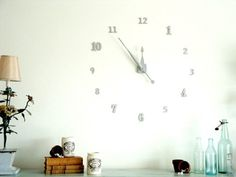 Make a custom clock for your wall using random wood house numbers, a clock mechanism, clock hands and spray paint.