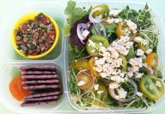 Mixed green salad with red onion slices, green and yellow plum tomatoes, sweet clover sprouts and mediterranean flavored vegan (soy) feta cheese on top. At top left is a cup of lentil & quinoa tabbouleh and at the bottom left are purple rice crackers for the tabbouleh and 2 dried apricots packed in an Easy Lunch Box.