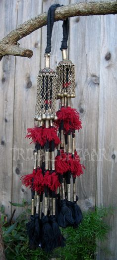 This is a traditional Turkmen tassel pair. They are hand crafted of hand braided silk that features beads, and metal bell caps.