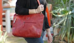 This classic red leather shoulder bag is bound to attract all eyes. A comfort hold and practical compartments puts this bag over the others, not to mention it's fair trade!