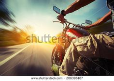 Biker riding motorcycle  on an empty road at sunny day - stock photo