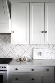 Love the vertical herringbone pattern with subway tile for backsplash - flourish design + style | gallery wall painting in our kitchen