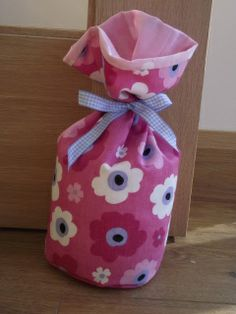 Door stop in funky pink daisy fabric from Prestigious fabrics with a pink polka dot lining from Laura Ashley. Tied with a blue gingham ribbon