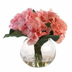 "Featuring faux pink-hued hydrangeas in a glass bubble vase, this lovely arrangement brings a touch of natural style to your decor.      Product: Faux floral arrangementConstruction Material: Silk, plastic, acrylic and glassColor: Pink and greenFeatures: Includes faux hydrangeasDimensions: 9"" H x 9"" Diameter"