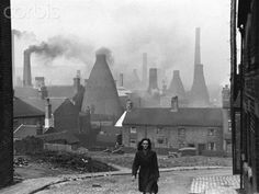 before the Clean Air Act. Stoke Street Scene by Kurt Hutton. A woman walking up a street in Stoke-on-Trent, Staffordshire, with smoking bottle kilns belonging to potteries visible in the background, 2nd March 1946.