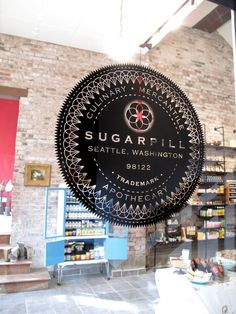 Sugar Pill Apothecary logo, suspended medallion signage.