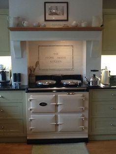 Aga cooker with extractor hood supported by plain corbels. You can buy similar cooker hood corbels online at www.buycarvings.co.uk