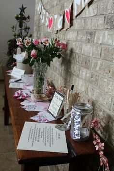 Bridal Shower entry table: MISS to MRS banner, date night jar, note cards for guests to write name/address/gift given, fresh flowers, and hand cut hearts from old excess scrapbook paper.