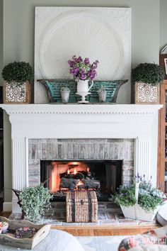 Fireplace mantel decorated for Spring- white/teal/purple theme.  Love those carved wooden boxes from Homegoods!