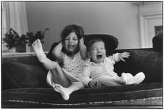 Photos by a famous photographer named Elliott Erwitt. He started taking photos in the and is known for his black and white documentary-style photographs. The charming photos are ones that depict everyday life, like siblings having a bad moment!