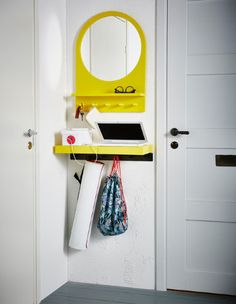 A small yellow wall shelf, hooks and mirror hang between a door fram and a corner, storing a laptop, phone, workout bag, yoga mat and glasses.