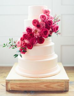 Cascading pink flowers on a simple white wedding cake - just lovely!