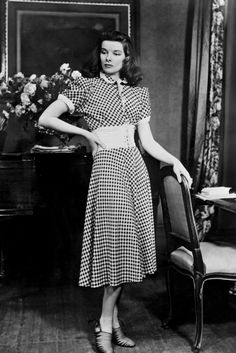 Katharine Hepburn wears a gingham dress with a peter pan collar on the set of The Philadelphia Story in 1940.