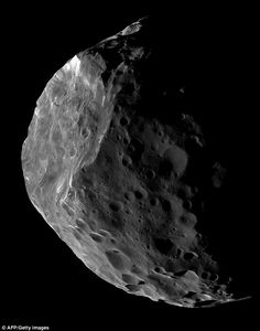 In a rare image, taken by the Cassini spacecraft, the distant satellite has been captured in all its pockmarked glory. Phoebe orbits at a staggering distance of 8,049,668 miles (12,952,000km) from the planet and, unlike Saturn's other moons, it sits in darkness, reflecting just 6 per cent of the sunlight it receives