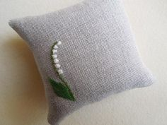 Lily of the valley pin cushion. Hand embroidered fully finished, tightly stuffed linen pinchusions are about 3 inches square. Hand made in Japan.  http://www.frenchneedle.com/collections/sale/products/lily-of-the-valley-pin-cushion#