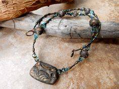 Necklace made with a stoneware clay pendant..seed beads... crystal beads… bronze beads., and beads made by me. by AtHomeInTaos on Etsy https://www.etsy.com/listing/208919804/necklace-made-with-a-stoneware-clay