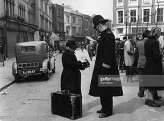 A policeman helps an old lady in Portobello Road market, west London. Original Publication: Picture Post - 5309 - All London - pub.1951
