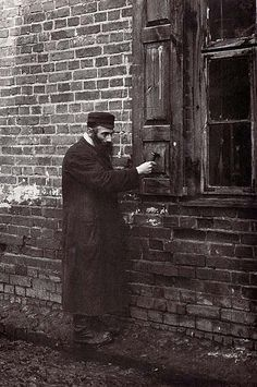 """The """"Shabes-Klaper"""" - On Friday evening he knocks on shutters announcing the beginning of the Sabbath. Lublin Provence, 1926"""