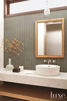 Gray and gold #accent a powder room with a glass mosaic backsplash and a marble countertop, both by Ann Sacks. See more at www.luxesource.com.