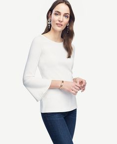 """Finished with feminine fluted sleeves, our refined knit top ends on the sleekest note. Boatneck. 3/4 sleeves. 25 1/2"""" long."""