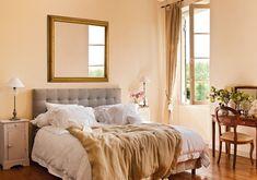 Luz y clasicismo en el dormitorio  Un gran espejo con marco dorado refleja y duplica la luz del dormitorio. Cabecero de lino con capitoné, similar deYute's. Escritorio, similar deGuadartey silla, similar deBecara. El mueble