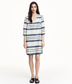 Striped dress in woven cotton fabric. 3/4-length sleeves, V-neck, and gently rounded hem. Unlined.