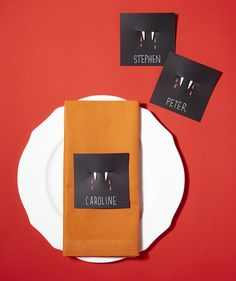 """Invite friends to sit for a bite. Cut a 2-inch-long slit into black note cards, about 1½ inches from the top and side edges. Break off the handle of a white plastic fork and clip the tines into the slit—the two outer tines on the front of the card, the two inner tines on the back. Using gel pens, draw """"drops of blood"""" in red and write the guest's name in white."""