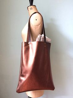 Simple copper leather tote bag - great for work documents, visits to the market and just about everything else. Made from soft bronze metallic leather with veg tan leather handles - the perfect length for slinging over your shoulder.  Unlined - natural suede interior. Flat construction  Approximate dimensions: Height: 16 inches / 41cm Width: 12.5 inches / 32cm  Strap: 11 inch / 28cm drop.