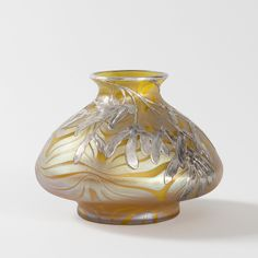 Austrian Iridescent Glass and Silver vase by Loetz A Bohemian Jugendstil glass vase with a pulled golden iridescent design against a yellow ground by Loetz. The vase is further ornamented with a silver overlay of seed pods descending from the neck of the vase