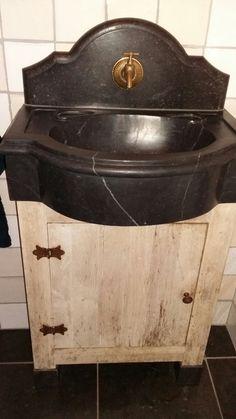 Toiletmeubel van eikenhout met massief hardstenen bak en uitgewerkte hardstenen achterplaat.