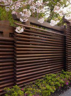 Louvre-achtig tuinscherm waarbij de planken schuin in de paal geplaatst zijn. Kan ook verticaal