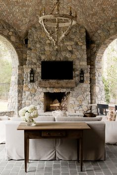 A large wooden chandelier and gorgeous stone fireplace lend a rustic feel to this chic outdoor living space. A small sofa and two armchairs provide seating.
