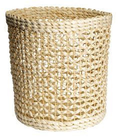 Storage basket in braided straw. Height 11 3/4 in., diameter at base 10 1/4 in.