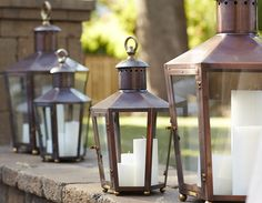 Copper lanterns from Bevolo Gas & Electric Lights line the low walls around the Vineyard Terrace - Traditional Home® / Photo: John Merkl
