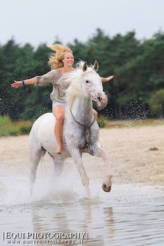 Bareback horse riding at the beach with girl flying her arms and horse splashing the water. Some casual bareback. Both horse and rider look amazing!