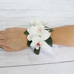 This gorgeous white orchid wrist corsage could easily be a tropical style, or a classically elegant style option. The orchids and greenery rest on a thick white satin ribbon that can be tied around yo
