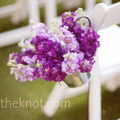 Galvanized buckets hung from shepherd's hooks along the aisle and were filled with monochromatic arrangements of purple flowers and stock.