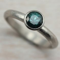 Our 5mm Classic Engagement Ring, customized with a rustic texture on the ring band. It has a fair trade Teal Blue Montana Sapphire set in 14k White Gold.