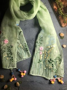Embroidered Linen Scarf with Fancy Corner Tassels packed in Signature Gift BoxThink wearable, sunny fields of soft blooms that encapsulate all things summer and slow fashion. Can you almost feel that warm breeze against your skin, carrying the lingering fragrance of a million dancing flowers?Our delicately embroidered cotton linen scarves are a dreamy escape into subtle bursts of colour and fable-like beauty that come alive with every handcrafted detail etched in thread. Throw one of these… Embroidery Scarf, Flower Embroidery Designs, Hand Embroidery Stitches, Embroidery Fashion, Floral Embroidery, Embroidery Patterns, Embroidered Clothes, Embroidered Gifts, Designer Scarves