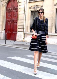 Mariana Cassou, sócia do Gallerist, com bata e saia mídi listradas em preto e branco, mini bag a tiracolo vermelha e sandálias brancas.