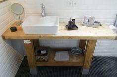 Un établi fait office de meuble de salle de bain. Décapé et raboté, il a été recouvert d'un vernis protecteur et personnalisé avec une plaque ancienne émaillée.