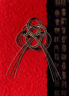 elegant use of mizuhiki knot in vibrant red, black and gold...