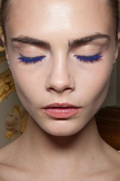 Cara shows off her electric blue lashes backstage at Stella McCartney Fall 2012