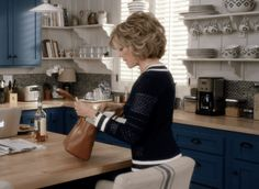 Grace and Frankie beach house kitchen with blue cabinets and white open shelves.