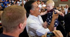 Mitt Romney holds a baby in Orange City, Iowa, on Sept. 7. | Reuters