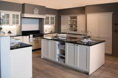 Klassieke keuken met Falcon fornuis.  Deze landelijke keuken heeft vooral de look van een klassieke keuken met enkele landelijke toetsen. De witte keukenkasten met kaderdeur, het werkblad in graniet, het Falcon fornuis, de wandtegels, alsook de kleur op de muren, alles past perfect samen en vormt een geheel. De keuken heeft een U-vorm en is daarnaast ook nog voorzien ven een eiland, dat kan dienen als opbergruimte, decoratieplaatsje of werkblad.