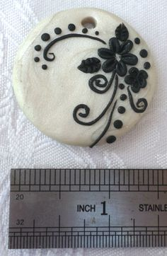 Polymer clay pendant, handmade with applique technique, one of a kind. Pearly white, with lacy black flowers, leaves, swirls and dots. By Lis Shteindel.