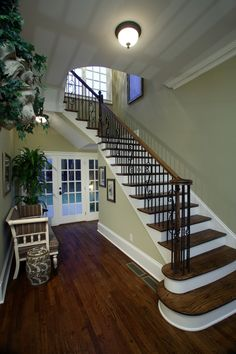 Very traditional staircase with a dark wood floor, glass doors leading to the backyard and a striped upholstered bench. Hardwood looks great in traditional homes, but faux wood tile could work as well. See why!