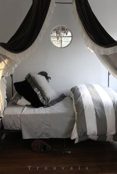 Grey bedding with a black canopy looks elegant.